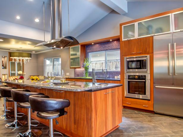 Gray Kitchen With Wood Cabinetry and Suspended Oven Hood