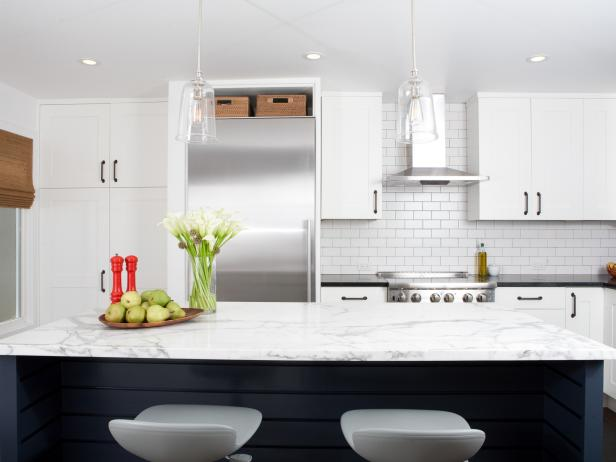 Eat-In Kitchen With White Cabinets and Black Island With White Counter