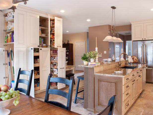 Brown Kitchen With White Pantry, Brown Island and Black Dining Chairs