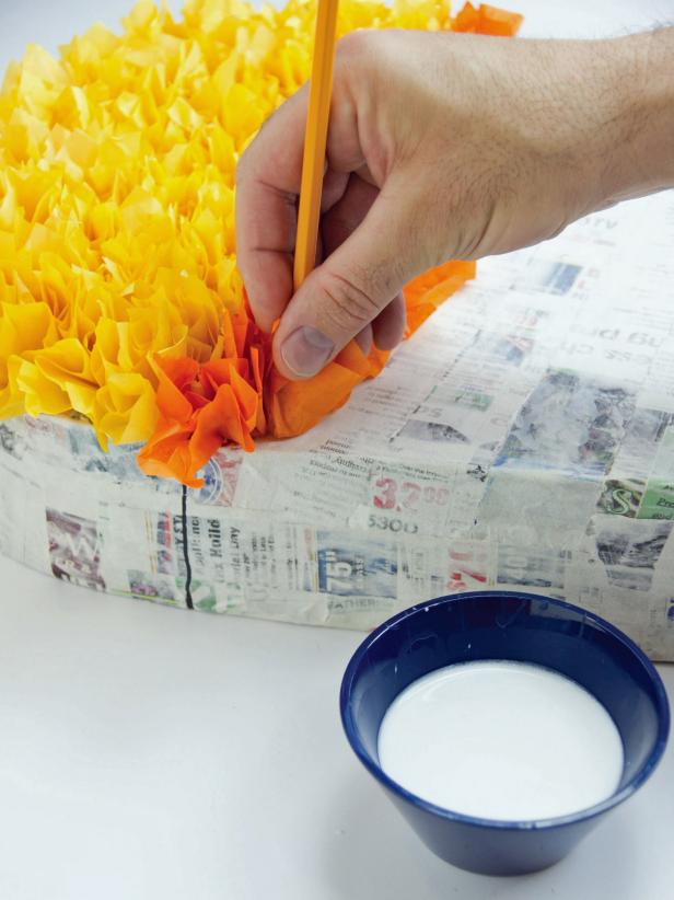 "Add the tissue paper to the piñata about 3/4"" apart to fill in the sections. Complete the top and sides."