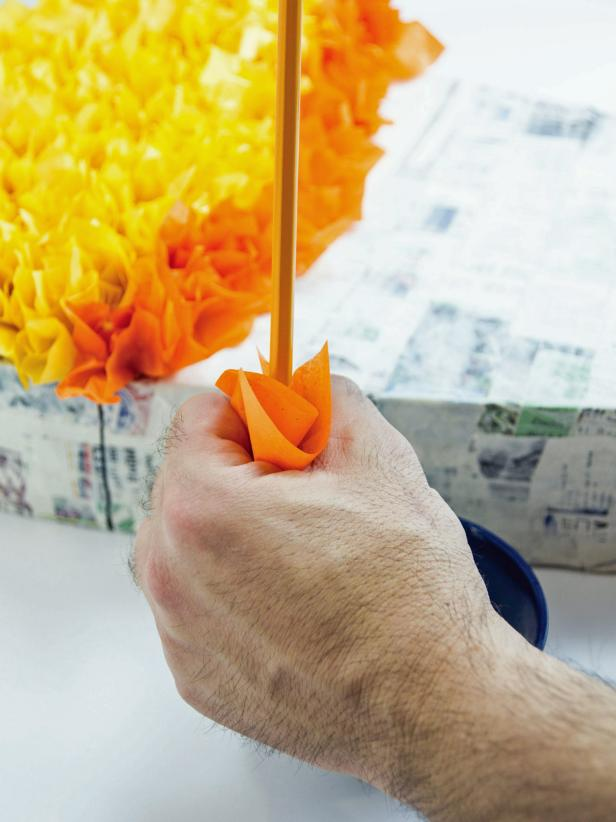 Fill in each section with the right candy corn color. To add tissue to the pinata make an 'O' with your forefinger and thumb. Lay a tissue square over the O and poke a pencil, erase end first, into the hole.