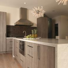 Sleek Modern Kitchen With Spiked Pendant Lights & Waterfall Island