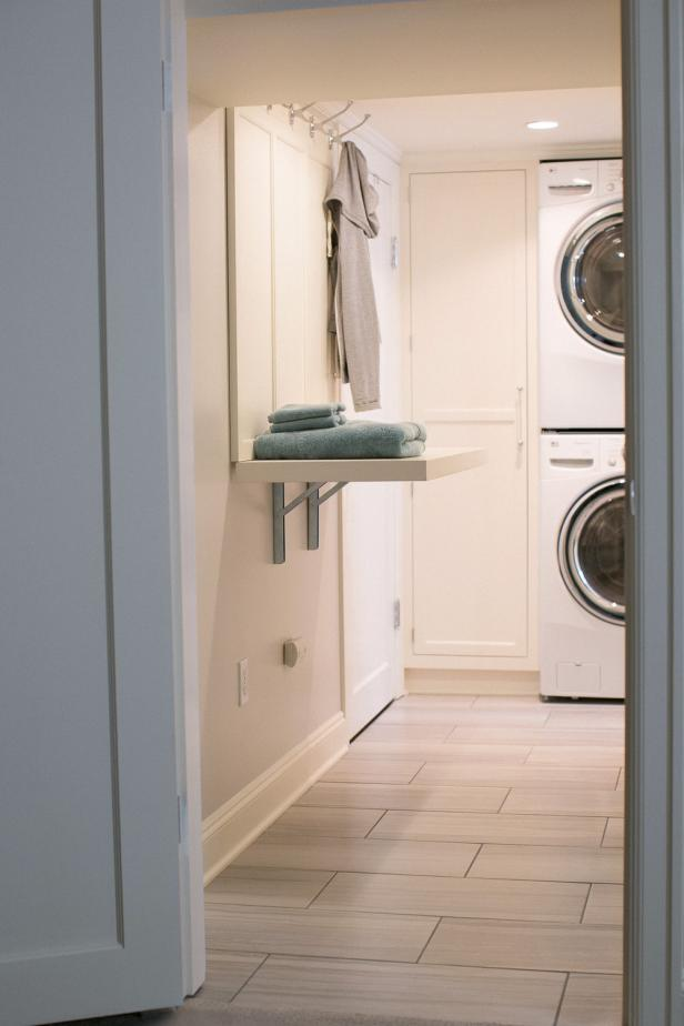 White Laundry Room With Folding Station, Coat Hooks, Stacked Units