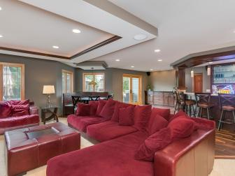 Transitional Home Theater Features Striking Red Sectional, Armchair & Ottoman