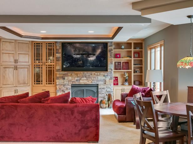 Basement Home Theater Features Red Accents, Television, Fireplace & Additional Game Space