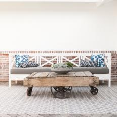 Front Porch Sitting Area With White Bench and Rustic Table