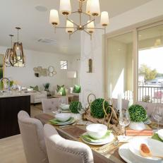Elegant Transitional Dining Space Featuring Shrub Centerpiece, Tufted, Nailhead  Dining Chairs And Contemporary Chandelier In Open Floor Plan