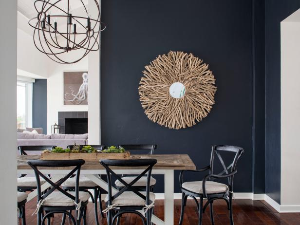 Dark, Navy Blue Walls in Contemporary Dining Room With Country Table, Spherical Chandelier and Driftwood Mirror Frame