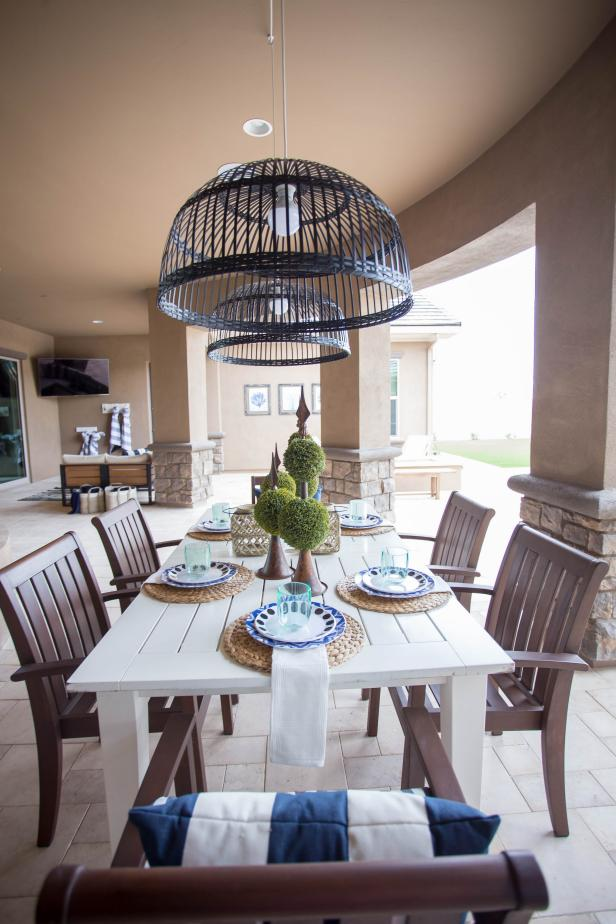 Farmhouse-style seating and basket chandeliers create a fun, casual vibe in this outdoor dining room. A covered patio creates a second living area in this glamorous transitional home.