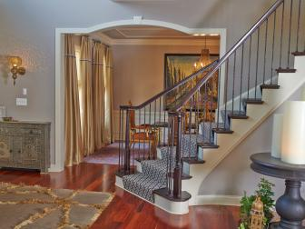Eclectic Foyer Features Eastern Influenced Cabinet, Sconce & Striking Spiral Staircase