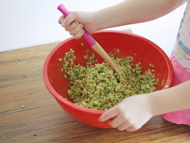 Stir ingredients to make spinach-dyed Rice Krispies treats with your kids this St. Patrick's Day.