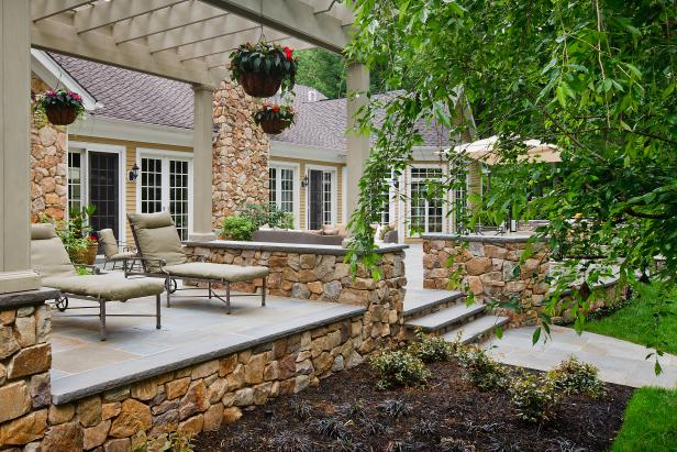Raised Stone Patio With Wood Pergola