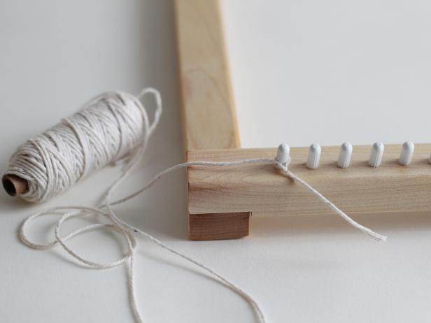 The weaving will be made of yarn that goes vertically, called the warp, and horizontally, called the weft. The first step is to create the warp on your loom with the thin, white cotton yarn. On the very left bottom peg, tie on the yarn. String the yarn up to the left top peg, around, and back down.