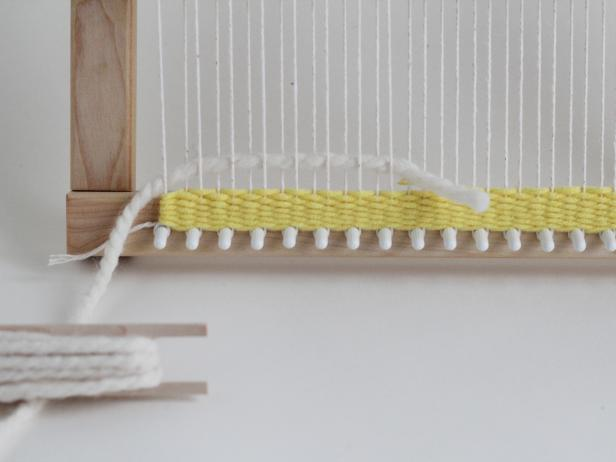 To switch colors, thread your next color halfway through the shed. Leave the tail of the yarn behind the tapestry. Weave a few inches of stripes in different colors.