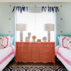 Girl's Bedroom With Coral Dresser and Light Blue Accent Wall