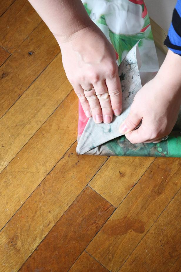 Hold the corner straight up in the air and flatten the fabric down to create a triangle. This will make a clean corner. Staple in place.