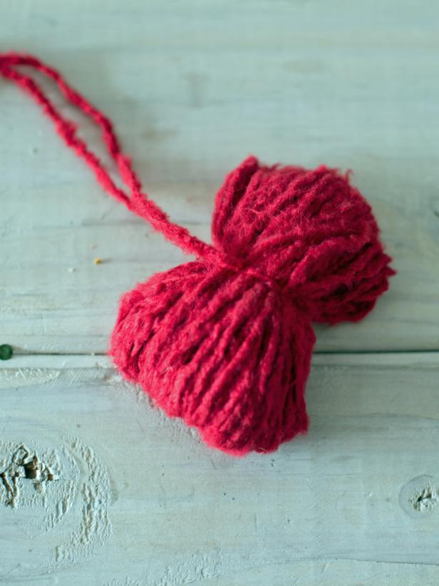 "Once yarn is tied, it should be in a ""bow-tie"" shape. Cut loops on each end of the ""bow-tie"" to make a pom-pom shape. Yarn can then be trimmed, so the pom-pom is a nice, round shape, or it can be left shaggy."