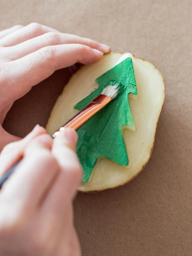 Use half-inch artist brush to paint raised design on the potato. Brushing the acrylic paint on makes the design more even, as opposed to pressing the potato directly into paint.