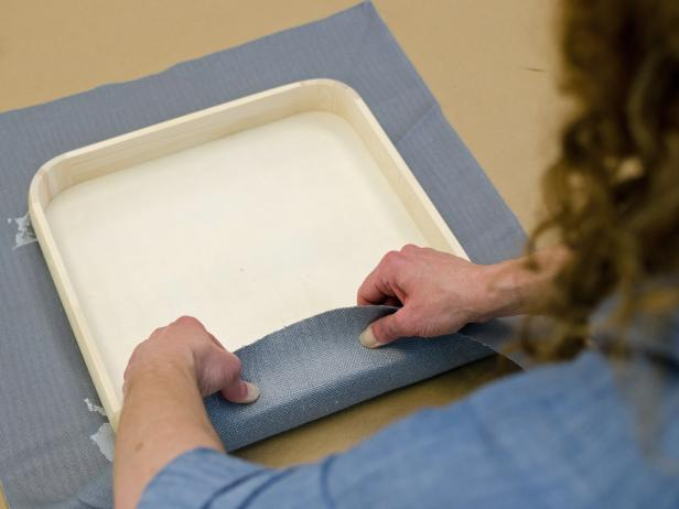 Pull fabric tightly around sides of tray before gluing in place.
