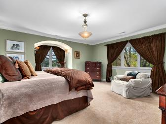 Impressive Bedroom Features Grand Window Treatment & Shimmering Bed Linens