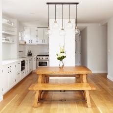 White Penthouse Kitchen With Globe Pendant Light Fixture
