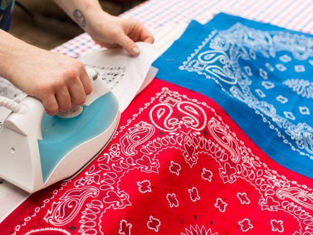 Roll out the webbing tape along one edge of a red bandana and trim to size and attach using an iron.