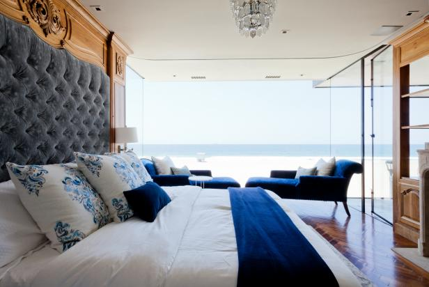 Seaside Master Bedroom with Large Windows, Blue Chaise Lounge Chairs, and a Built-in Headboard