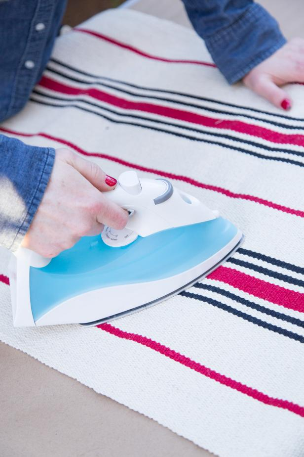 Lay the rug flat and use a hot iron to remove any folds or creases.