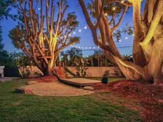 Enchanting Backyard Featuring Sting Lights, Wood Stage and Stairs Leading To an In-Tree Patio