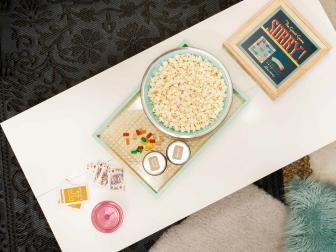 Layered Textured Rugs Under Dorm Room Table With White Tabletop and Gold and Turquoise Breakfast Tray