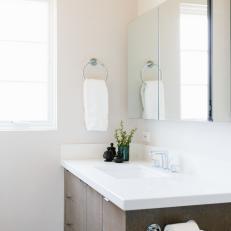 white minimalist bathroom with mirrored medicine cabinet