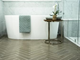 Brown Herringbone-Patterned Floor Tile Showcases Modern Tub in Updated Bathroom