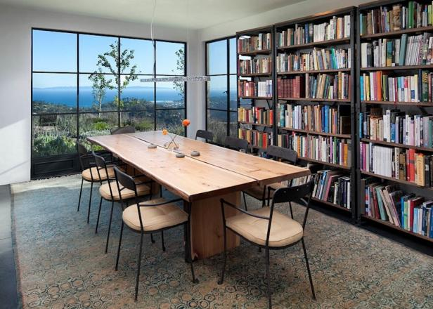 Dining Room With Large Windows, Row of Bookshelves & Wood Table