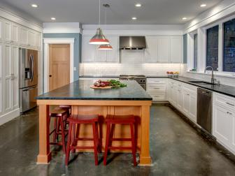 Bright, Contemporary Kitchen With Large Wood Island, Red Barstools and Concrete Floor