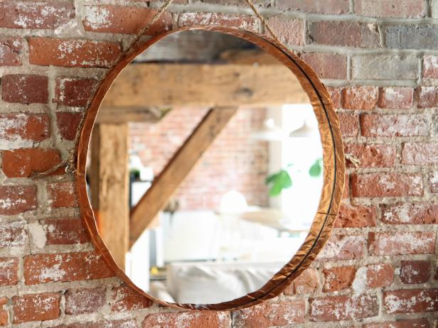 Make a hanging round mirror with copper edging to add a stylish touch to any room in your home.