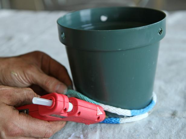 Apply glue and wrap the rope around the plastic pot, working one section at a time.