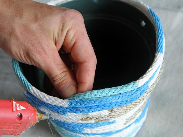 Secure the end of the rope to the inside lip of the pot using hot glue.