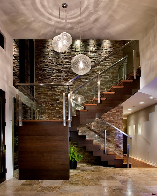 Contemporary Foyer With Glass Pendants, Staircase and Stone Wall
