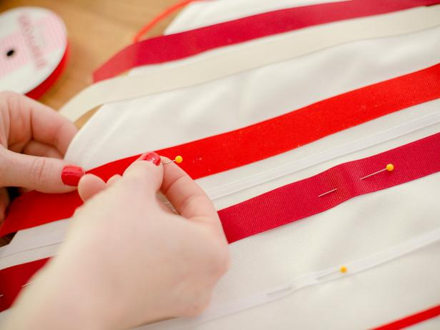 Roll out the ribbons in a diagonal across the pillow cover, alternating ribbon color and type, cut so that there is a 1 inch overhang on either side. Leave the spacing between ribbons slightly random and pin into place, as you work your way down.