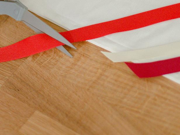 Once the ribbons are adhered to the pillow cover, neatly trim the excess ribbon along the edges.