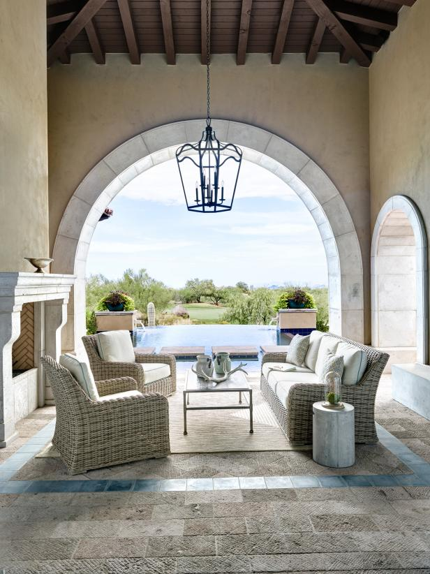 Neutral wicker furniture is combined with a glass coffee table and elegant lantern chandelier for a comfortable outdoor seating area. Exposed wood ceiling, stucco walls and textured neutral brick patio evoke a southwestern feel, overlooking the beautiful pool area.