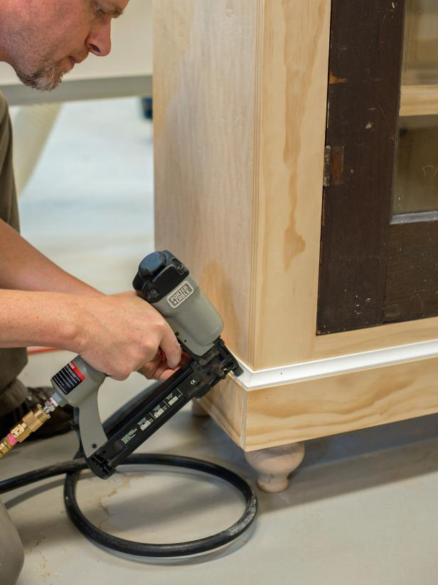 "With brad nails (1-1/4"" or 3/4"" depending on size of trim), tack in 1 x 4"" boards, cut to size, into top and bottom of cabinet. Add decorative molding as desired, cutting to size of a miter saw. Paint, stain or finish as desired."