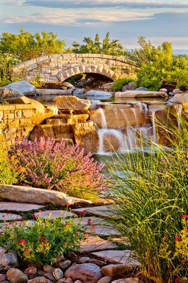 A Custom Stone Bridge Crosses Over A Naturalistic Pond