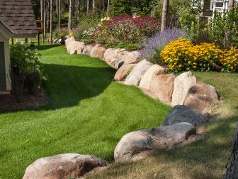 Gorgeous, Colorful Raised Flower Garden Lined With Large Rocks in Side Yard