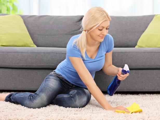 Young blond woman cleaning a carpet in front of a gray sofa