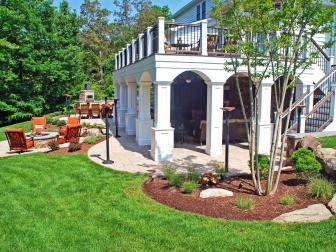 A White Dual Purpose Deck Adjoins a Lush Green Lawn and Fire Pit