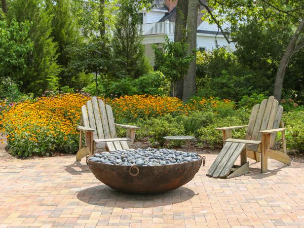 Fire Pit And Adirondack Chairs In Backyard
