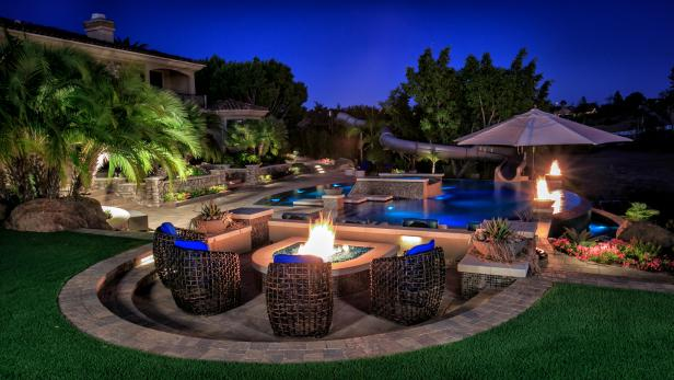 Stone Tile Fire Pit Patio Above Luxurious Swimming Pool and Tropical Landscaped Yard