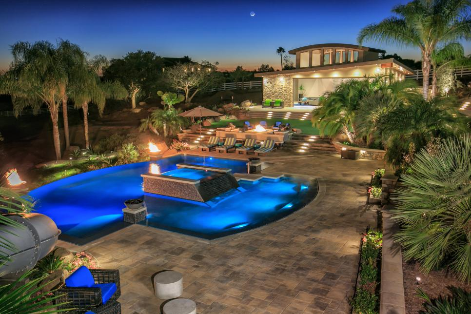 Tropical pool oasis with water features and fire pit for Garden oases pool