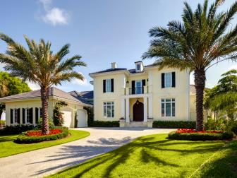 Classy, Traditional Home Exterior With Flower Bed Palm Trees and Light Brick Driveway